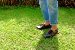 Fashion Man is Legs in Blue Jeans and Wear Vintage Shoes on Green Grass Background. Great for Any Use Royalty Free Stock Image