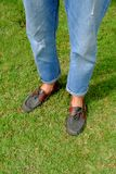 Fashion Man is Legs in Blue Jeans and Wear Vintage Shoes on Green Grass Background. Great for Any Use Stock Photos