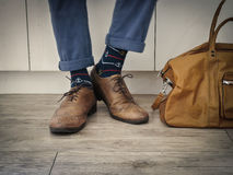 Fashion man legs in indigo navy blue pants, navy anchor socks, leather shoes and leather tote bag Stock Photo
