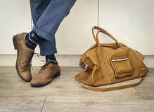 Fashion man legs in indigo navy blue pants, navy anchor socks, leather shoes and leather tote bag Stock Photos