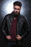 Fashion man with long beard pulling on his leather jacket Royalty Free Stock Photography
