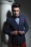 Fashion man looking down while closing his jacket Royalty Free Stock Photography