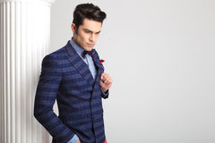 Fashion man looking down and fixing his jacket. Stock Photography