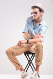 Fashion man looking down while sitting on a stool Royalty Free Stock Photo