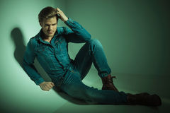 Fashion man lying on the floor, fixing his hair. Stock Photography