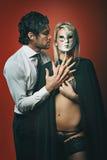 Fashion man with masked woman Royalty Free Stock Photo