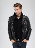 Fashion man, model leather jacket, gray background. Fashion man, Handsome serious beauty male model portrait wear leather jacket, young guy over gray background Stock Photo