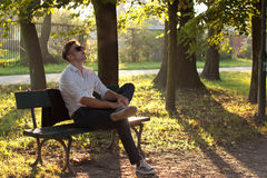 Fashion man in the park. Male model sitting in the park at sunrise Stock Image