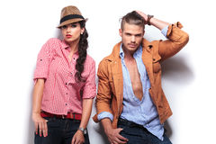 Fashion man passing his hand through his hair near girlfriend. Young casual fashion men passing his hand through his hair while his girlfriend poses with hands stock photography