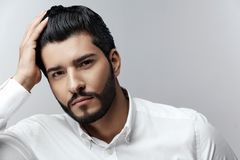 Fashion Man Portrait. Male Model With Hair Style And Beard. Handsome Man Touching Healthy Black Hair. High Resolution stock images