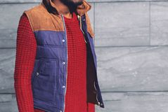 Fashion man in a red knitted sweater, vest jacket stands stock images