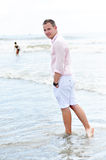 Fashion man on shore walking with foot in water. Portrait of a young man enjoying a walk on the beach wearing white shorts and pale pink shirt with a satisfied Royalty Free Stock Image