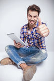 Fashion man sitting andz showing thumbs up gesture Royalty Free Stock Photography
