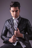 Fashion man sitting while fixing his leather jacket. Stock Photography