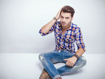 Fashion man sitting on the floor while fixing his hair. Royalty Free Stock Images