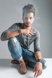 Fashion man sitting on the floor while holding a cigarette Royalty Free Stock Photo