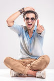 Fashion man sitting with his legs crossed. Happy young fashion man sitting with his legs crossed while holding one hand on his hat and showing thumbs up gesture Royalty Free Stock Images