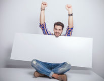 Fashion man sitting  while holding a empty billboard. Royalty Free Stock Photo