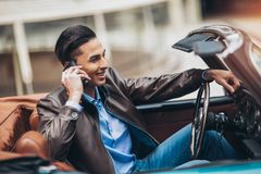 Fashion man sitting in luxury retro cabriolet car. Outdoors using phone royalty free stock photography