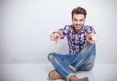 Fashion man sitting and pointing at the camera. Royalty Free Stock Images