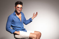 Fashion man sitting while presenting something to his left. Handsome young fashion man sitting on a stool with his hand in pocket, presenting something to his Stock Photography