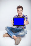 Fashion man sitting while showing you the computer screen Royalty Free Stock Images