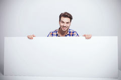 Fashion man smiling while holding a big white billboard. Stock Photos