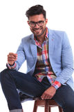Fashion man smiling to the camera while sitting Royalty Free Stock Image