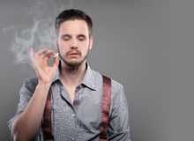 Fashion man smoking a cigarette on gray background. Royalty Free Stock Images