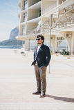 Fashion man standing on a embankment near beautiful modern building Royalty Free Stock Images
