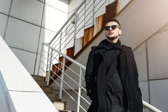 Fashion man in total black, standing on stairs, looking away. Closeup of young fashion man in total black, standing on stairs, looking away thoughtfully Stock Image