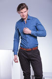 Fashion man is unbuttoning his shirt with one hand Royalty Free Stock Photos