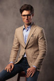 Fashion man wearing glasses and sitting Royalty Free Stock Photography