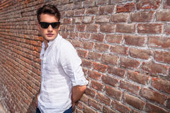Fashion man wearing sunglasses, leaning on a brick wall. Royalty Free Stock Photography