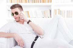 fashion man wearing sunglasses talking on the phone relaxed indoors stock images