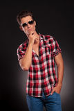 Fashion man wearing sunglasses and thinking Royalty Free Stock Images