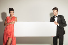 Fashion man and woman holding a blank board. Royalty Free Stock Image