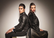 Fashion man and woman sitting back to back Stock Image