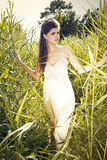 Fashion in a meadow. Young woman wearing white dress in a meadow Royalty Free Stock Photos