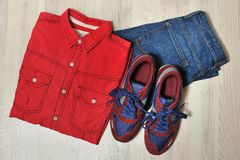 Fashion men`s casual outfit on wooden table, blue jeans pants, sneaker, top view Royalty Free Stock Image