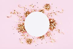 Fashion mockup with golden bows, serpentine and star confetti on pink pastel table top view. Flat lay for birthday or christmas. Fashion mockup with golden bows royalty free stock photo