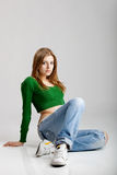 Fashion Model. Beautiful young fashion model seated on the floor Stock Image