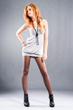 Fashion model. Attractive red-haired girl wearing beautiful dress and high heels shoes. Studio shot Stock Images