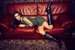 Fashion model. Young fashion female model in short green dress and high heel boots pose on red leather sofa Royalty Free Stock Images