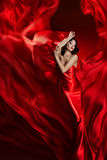 Fashion Model Art Dress, Woman Dancing in Red Waving Fabric. Beautiful Girl on Artistic Cloth background royalty free stock images