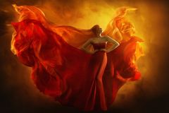 Fashion model art fantasy fire dress, blindfolded woman dreams. In red flying gown, girl beauty portrait, fabric fluttering like flame wings stock images