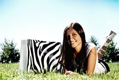 Fashion model with bag on a grass. Royalty Free Stock Image