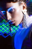 Fashion model beautiful girl in fashionable clothes in ultraviolet light, showing different poses. Beauty body and face. Royalty Free Stock Photos