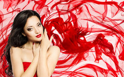Fashion Model Beauty Portrait, Woman over Red Waving Silk Cloth. Background, Beautiful Girl Fabric Makeup Stock Photo