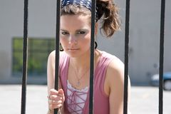 Fashion model behind iron bars. Twenty something fashion with mad expression behind bars Royalty Free Stock Image